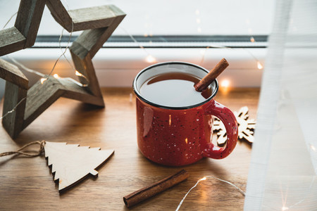 Black tea with cinnamon in a red mug among winter decor and lights  Cozy winter time still life