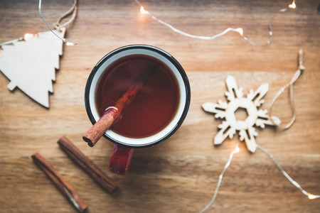 Top view of black tea with cinnamon in a red mug among winter decor and lights  Cozy winter time still life