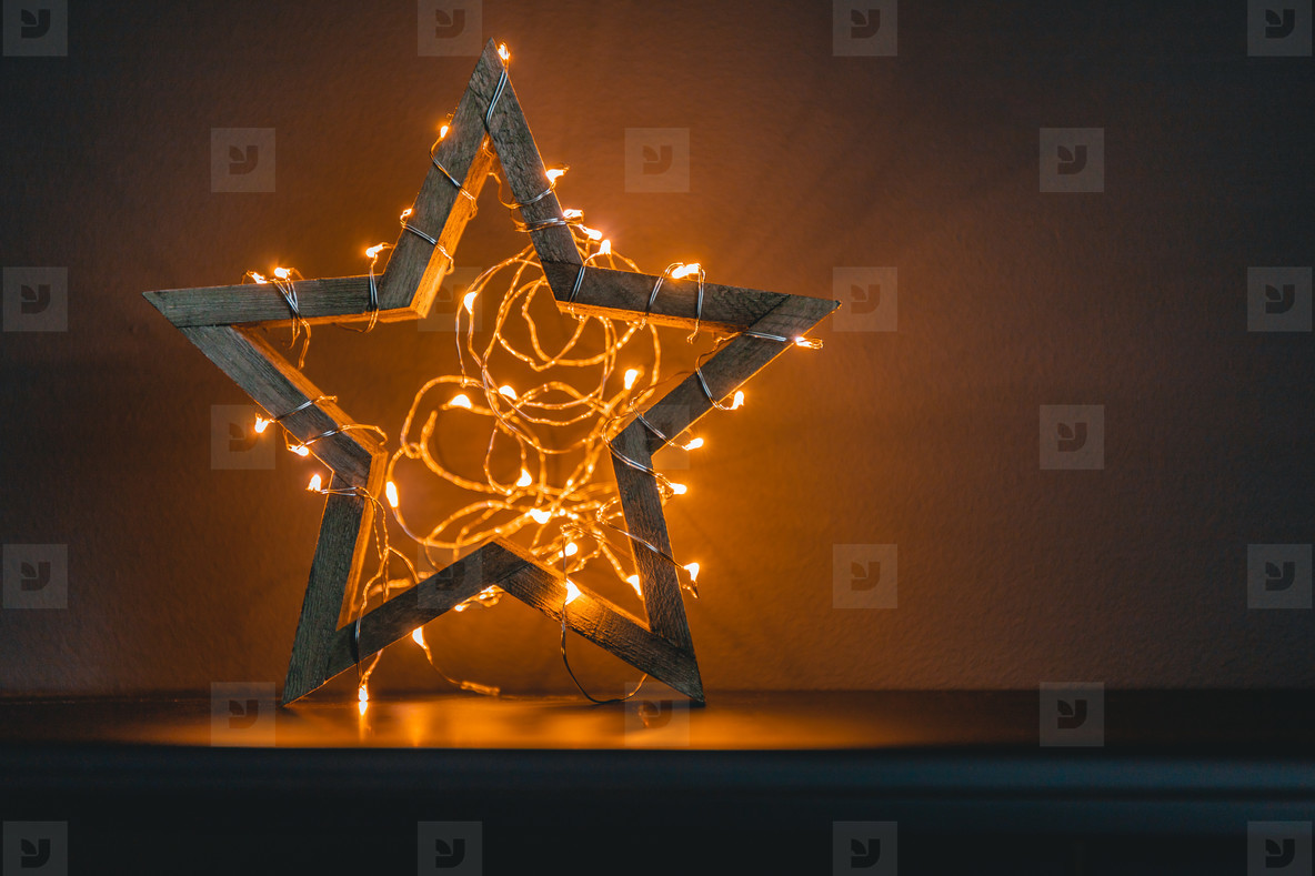 Wooden shiny star with a festoon as a symbol of New Year Holidays and Christmas  Copy space