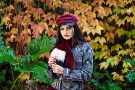 Young beautiful girl with very long hair wearing winter coat and cap in autumn leaves background