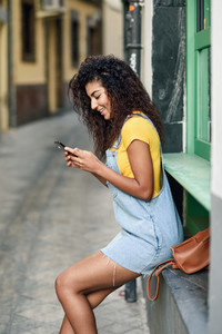 Young Arab girl looking at her smart phone outdoors