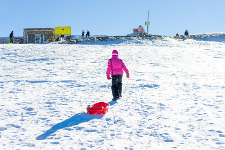 Little girl sledding at Sierra Nevada ski resort