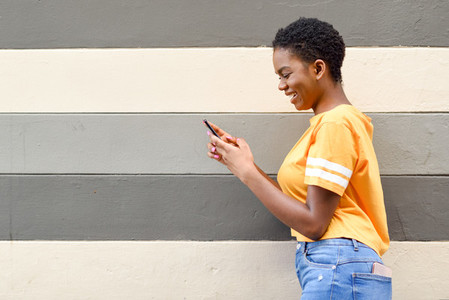 Young black woman laughing using her smart phone outdoors