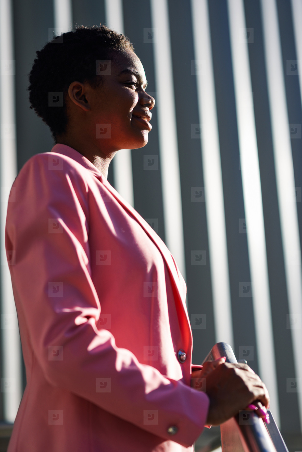 Smiling black businesswoman standing near business office building