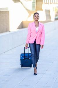 Black woman walking with travel bag wearing pink jacket