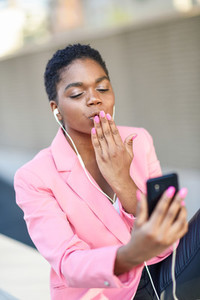 Black businesswoman sitting outdoors speaking via videoconference with her smart phone