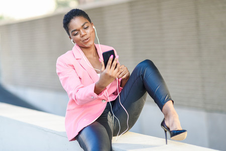 Black businesswoman sitting outdoors speaking via videoconference with her smartphone