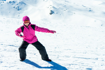 Little girl playing snowboard trainer on snow