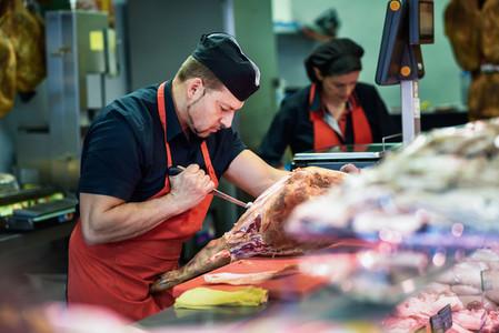Butchers boning a ham in a modern butcher shop