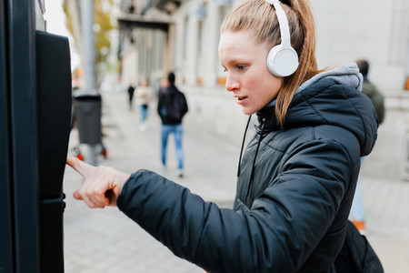 Young woman paying on parking meter in the city with jacket