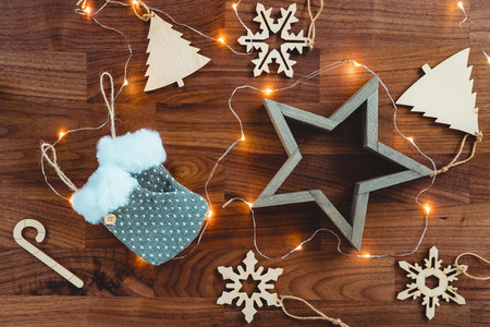 Festive Christmas or New Year flat lay with wooden fir toys and festoon on a wooden background