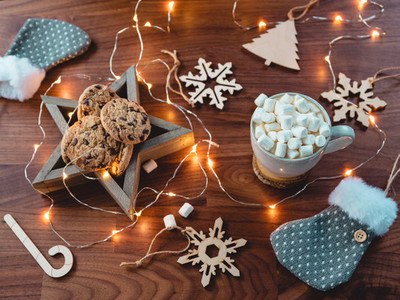 Cosy Christmas or New Year  flat lay Hot chocolate with marshmallow in a white ceramic mug among winter decor and lights