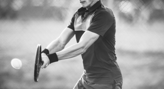 Tennis player hitting backhand in black and white