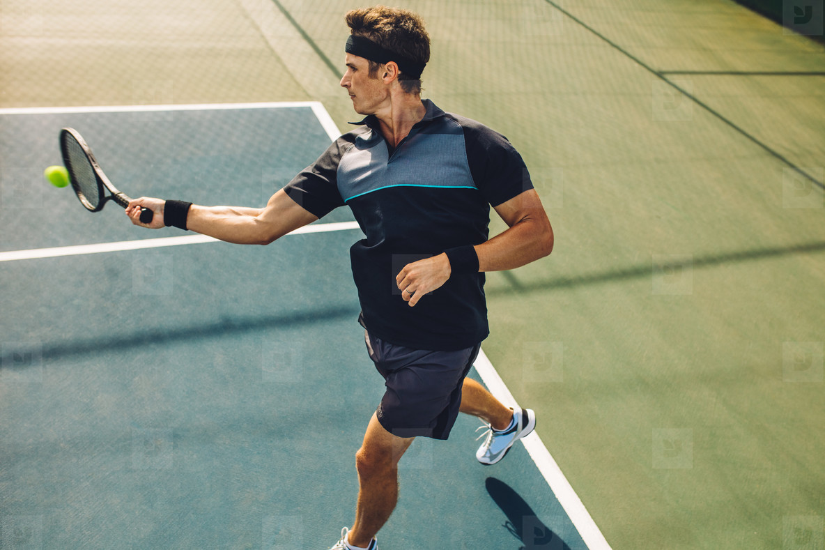 Tennis player practicing forehands from baseline