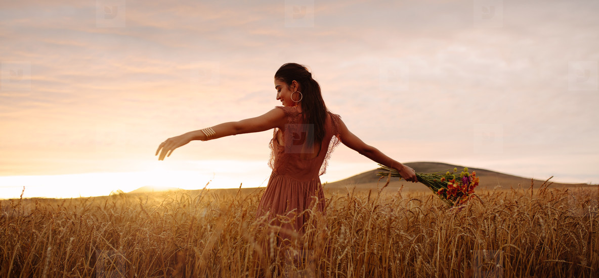 Happy woman enjoying in wheat field