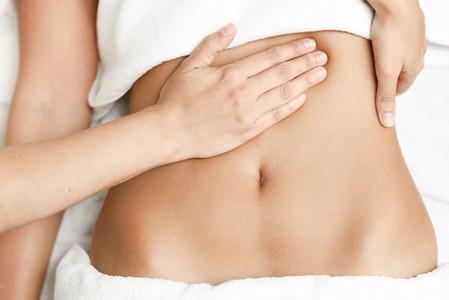Hands massaging female abdomen Therapist applying pressure on belly
