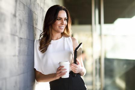Smiling businesswoman taking a coffee break in an office building