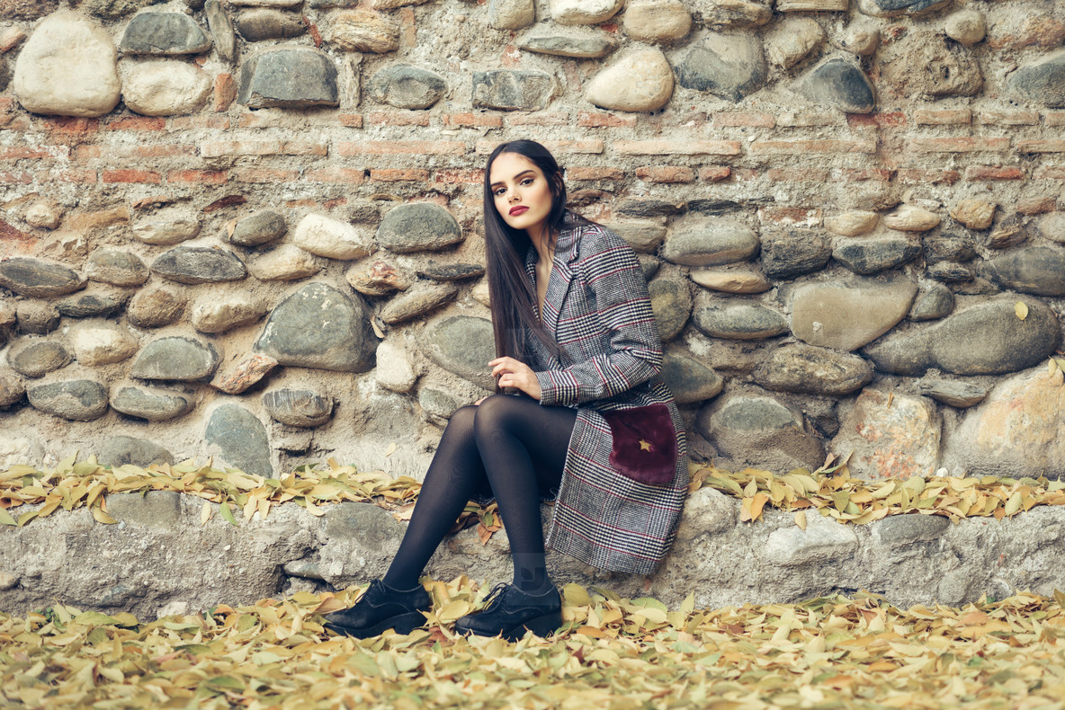 Beautiful girl wearing winter coat sitting on the floor of an urban park full of autumn leaves