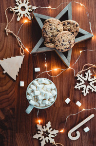 Cozy Christmas or New Year  flat lay Hot chocolate with marshmallow in a white ceramic mug among winter decor and lights Top view