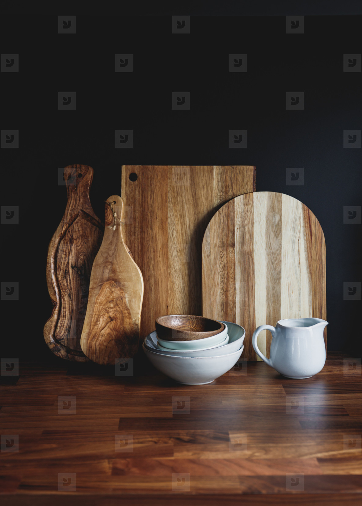 Set of wooden cutting board and ceramic dishes on a wooden kitchen table over black background  The concept of modern style rustic kitchen interior