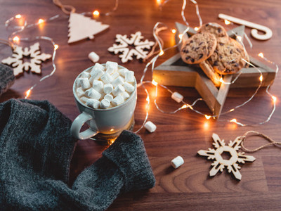 Cozy Christmas or New Year  flat lay Hot chocolate with marshmallow in a white ceramic mug among winter decor and lights