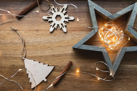 Top view of festive Christmas or New Year flat lay with wooden fir toys and festoon on a wooden background