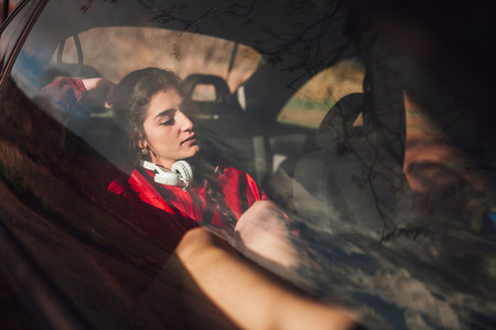 Young woman takes refuge inside a car while it rains