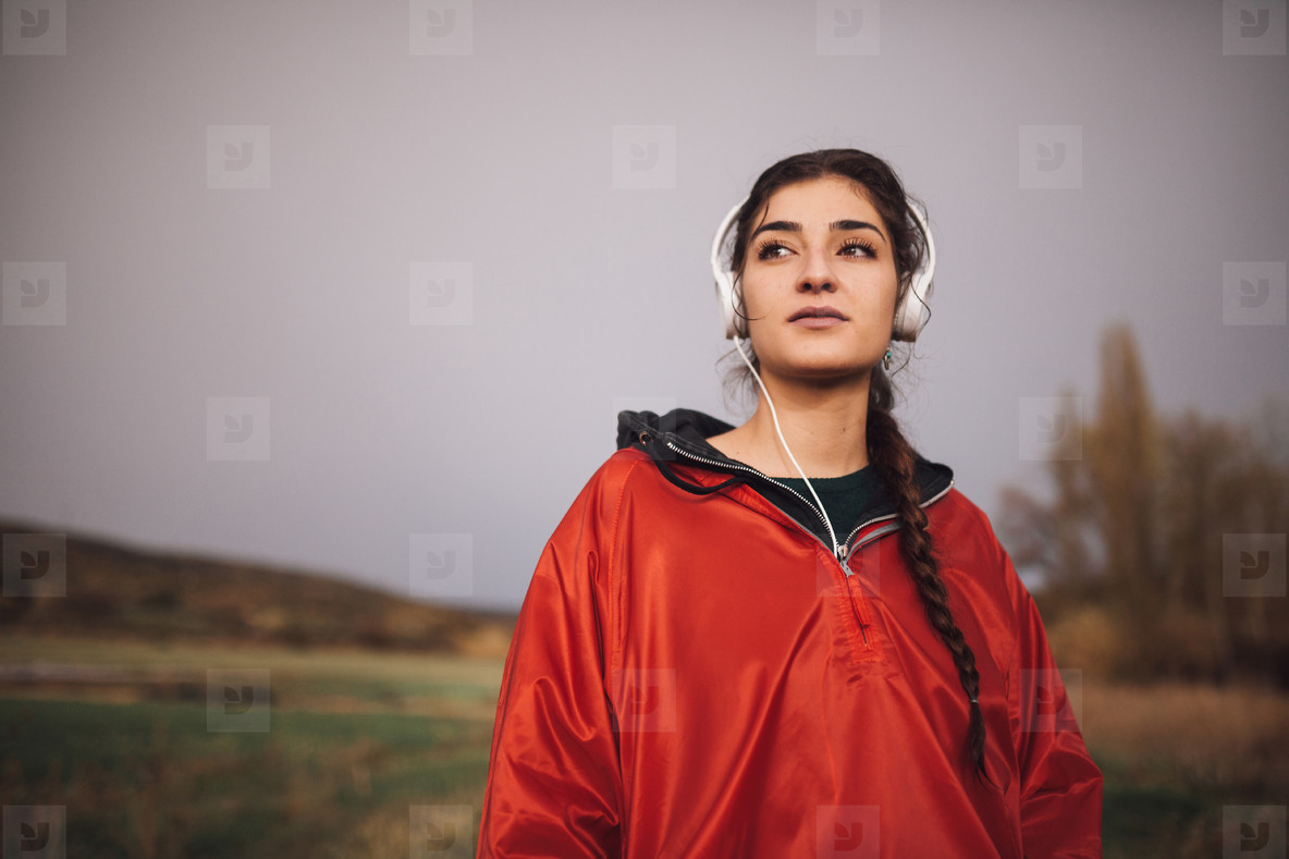 Young woman standing with raincoat listening to music on field