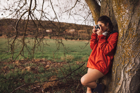 Young woman taking a photo with old camera wear a red raincoat