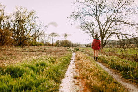 Young woman walking wearing a red raincoat in a rainy day