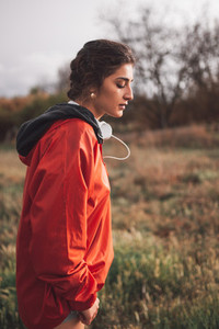 Young woman standing with raincoat and headphones on the field