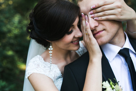 Charming bride closes eyes to her husbend from behind