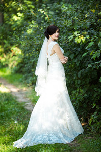 Beautiful bride in a gorgeous dress posing in a pine forest