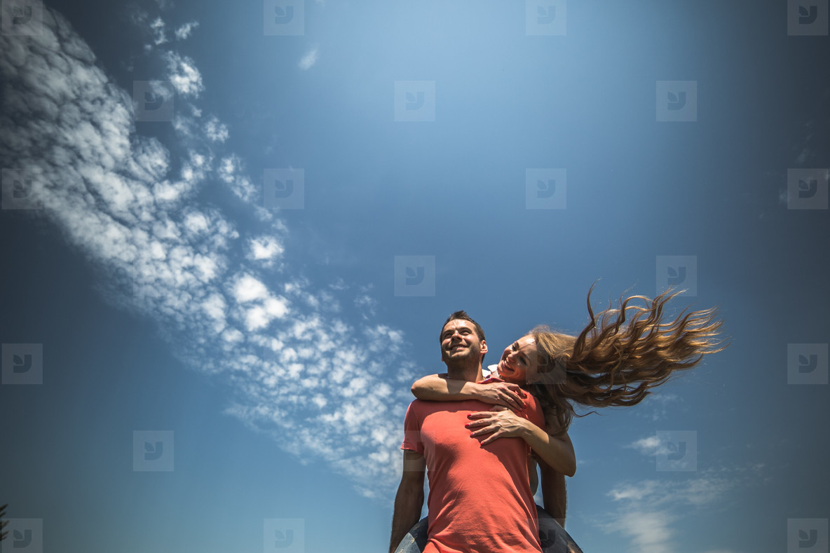 Girl hug her boyfriend from behind on background of sky