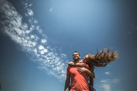 Girl hug her boyfriend from behind on background of sky