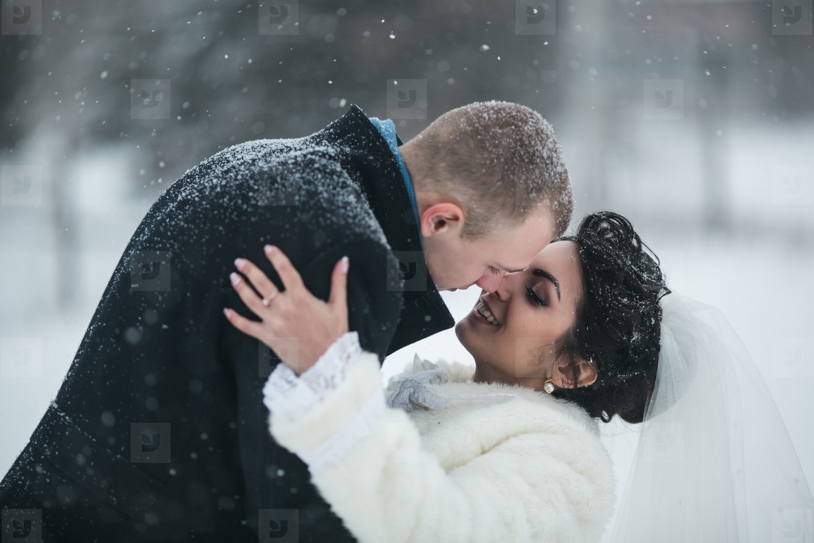 Bride and groom walking on the European city in the snow