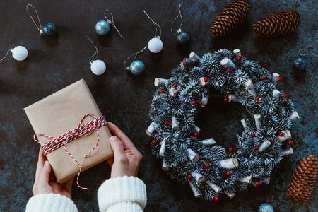 Girls hands in a winter white sweater hold a New Years gift box in craft paper on a table among Christmas decor Top view flat lay