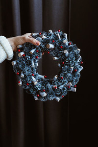 Womans hand in a winter white sweater holds a Christmas holiday wreath over dark background