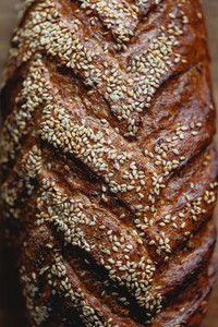 Close up view of whole grain loaf bread crust with sesame