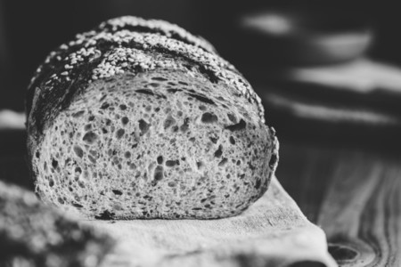 Whole grain loaf bread with chia seeds on a cutting board  Healthy eating concept  Black and white photography