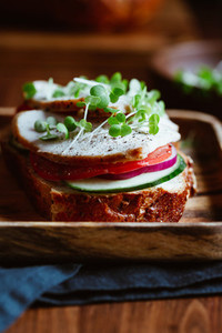 Sandwich with turkey breast and fresh vegetables served with microgreens on a wooden plate The concept of healthy and diet eating