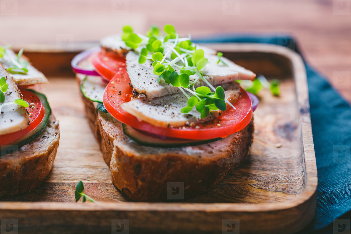 Sandwiches with turkey meat and fresh vegetables served with microgreens on a wooden plate  The concept of healthy and diet eating
