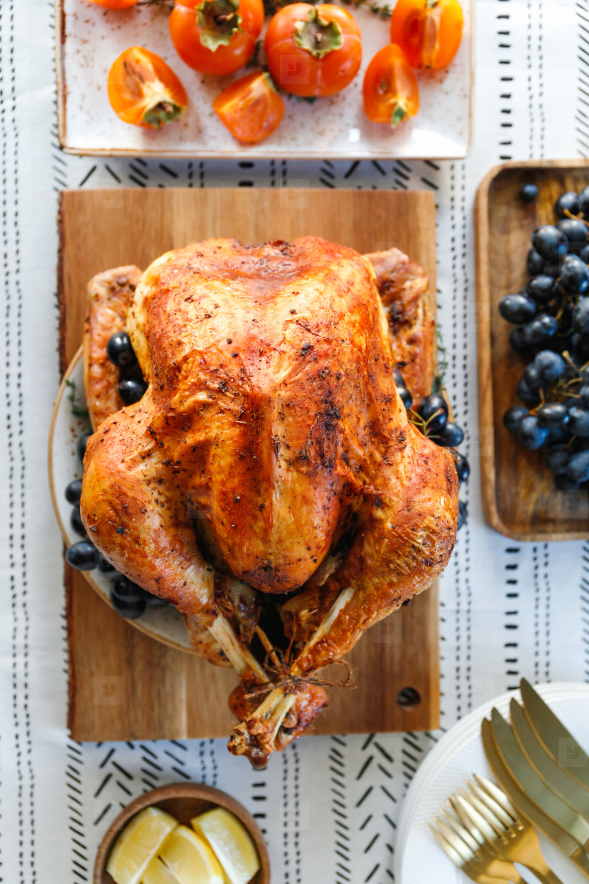Roasted whole turkey on a table with persimmon  blue grape and lemon for family Thanksgiving Holiday  Top view  flat lay