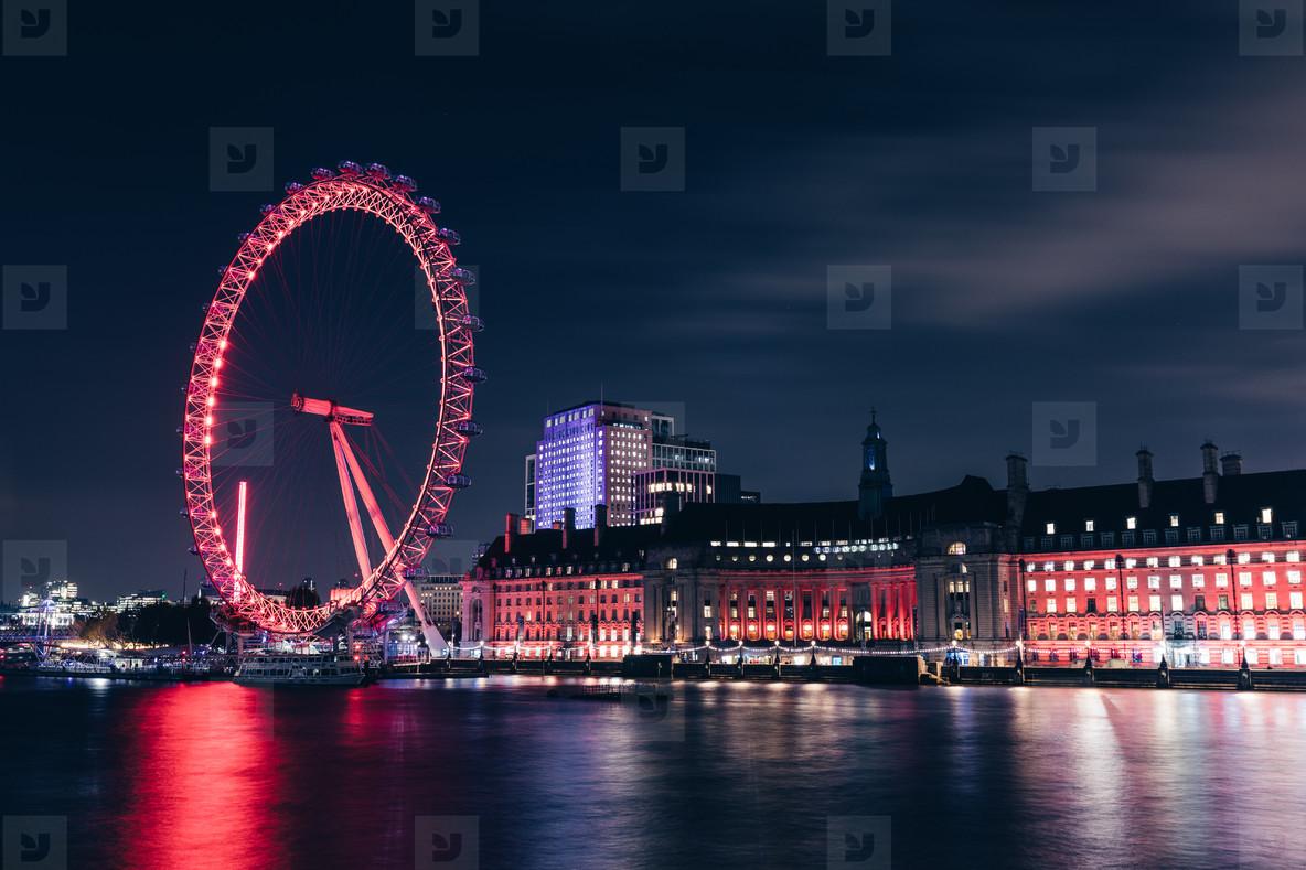 London eye wheel on modern city skyline at night