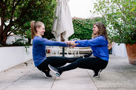 Two young women doing exercise together on a terrace