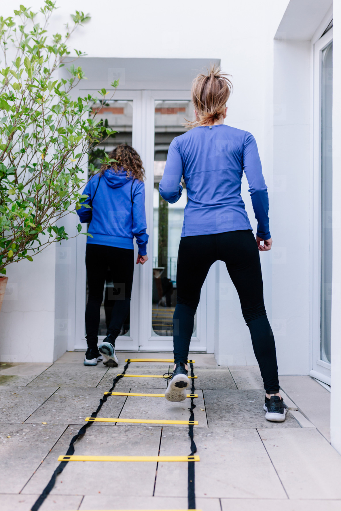 Two young women doing agility ladder exercise on a terrace
