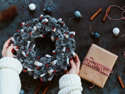 Girls hands in a winter white sweater hold a Christmas holiday wreath on a blue table among by New Years decor Top view flat lay