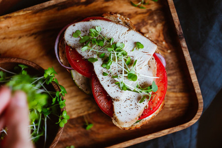 Sandwich with turkey meat and fresh vegetables served with microgreens on a wooden plate Top view flat lay macro food photography