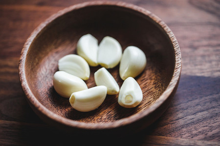 Macro food photography of peeled garlic cloves in a wooden bowl  Top view