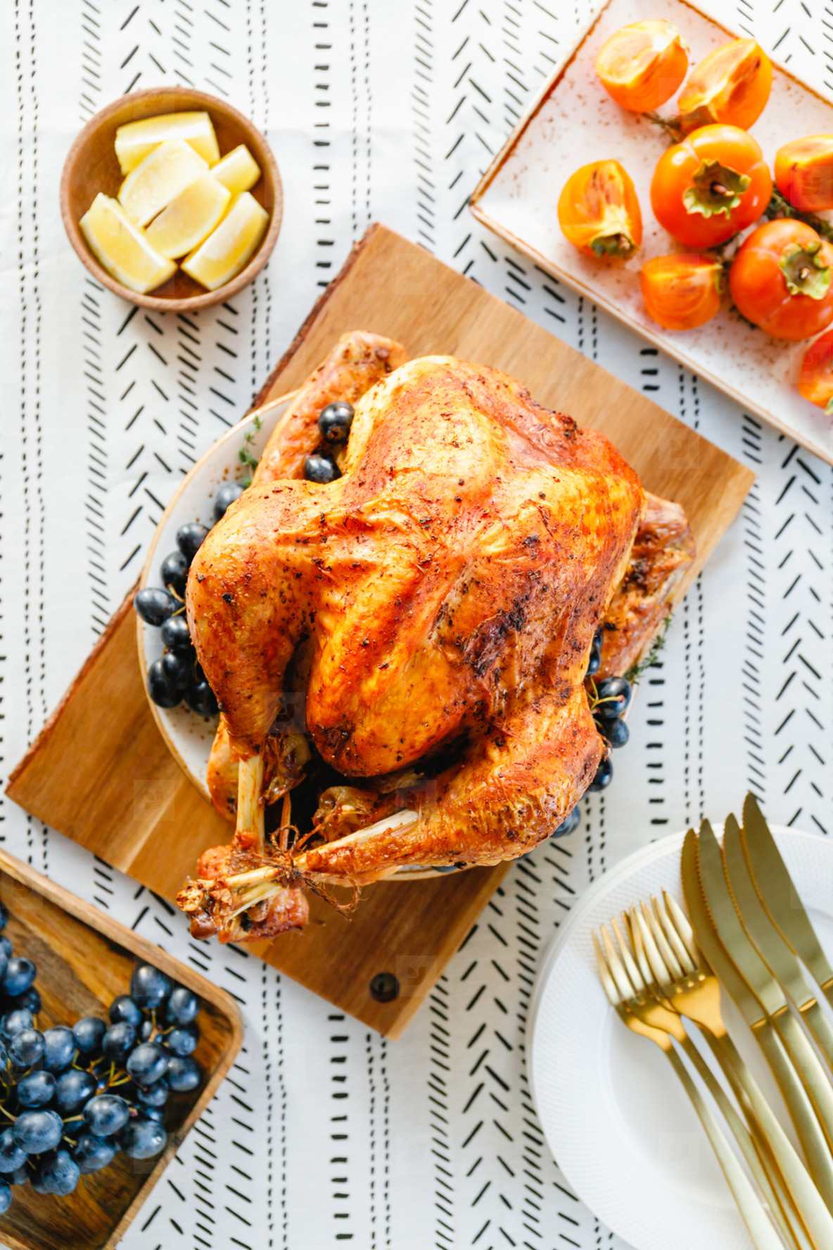 Roasted whole turkey on a festive table with persimmon  blue grape and lemon for family Thanksgiving Holiday  Top view  flat lay